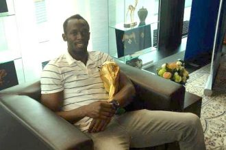 Usain Bolt Hold The Official FIFA World Cup In Brazil [PHOTO]